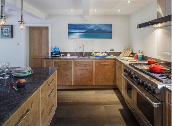 Kiểu dáng chữ L của mẫu tủ bếp gỗ xoan đào giúp tiết kiệm diện tích căn phòng